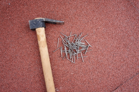 do it yourself: Do it yourself, hammer with nails on red roof shingles Stock Photo