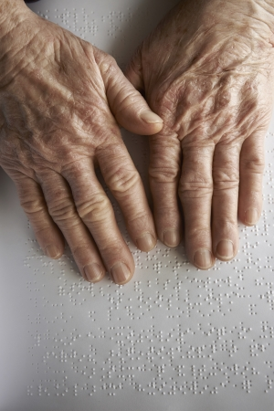 Old womans hands, reading a book with braille language photo