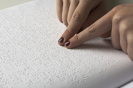Blind woman reading text in braille language photo