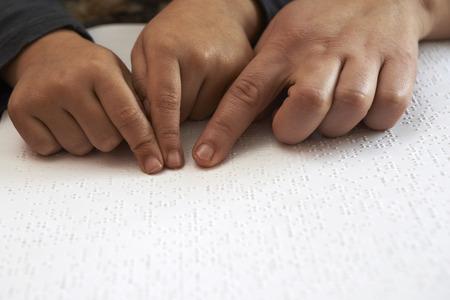 onderwijzen blid kind om de tekst in braille taal lezen
