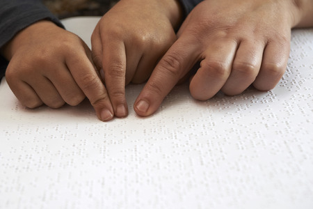 teaching blid kid to read text in braille language Stock Photo