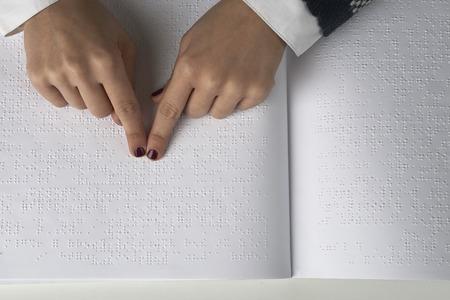 盲目の女性が点字の言語でテキストを読む