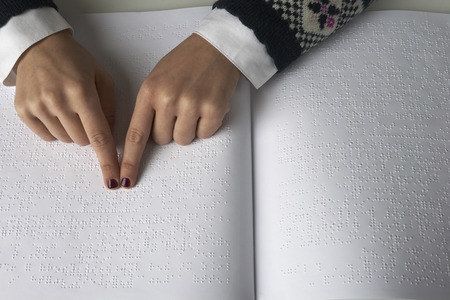 Braille: Blind woman reading text in braille language