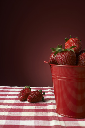 fresh red strawberries in a red bowl on checkered tablecloth, with red background Stock Photo