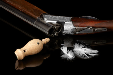 decoy: wooden whistles for calling ducks with a feather and a hunting gun.