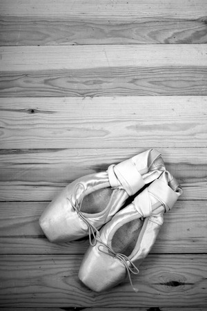 Black and white photo,  pair of ballet shoes pointes with ribbons on wooden floor