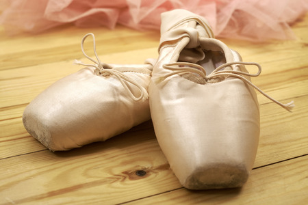 pointes: pair of ballet shoes pointes with ribbons on wooden floor Stock Photo