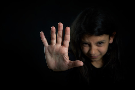 Children violence  Girl with her hand extended signaling to stop  photo