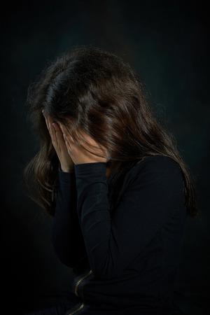 肖像画泣いている女の子の彼女は彼女の顔を覆っています。 写真素材