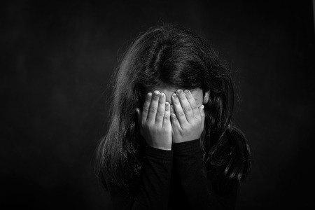 domestic: Black and white photo  Portrait of a crying girl  She is covering her face  Stock Photo
