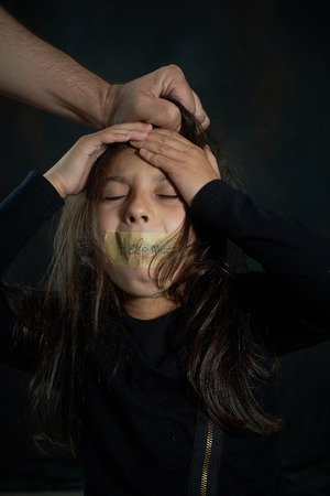 Girl cries as a guy pulls her hair while her mouth is closed with tape writing help me  photo