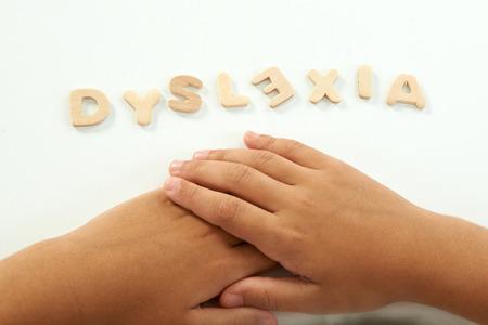 handen van een meisje vormen het woord dyslexie met houten letters