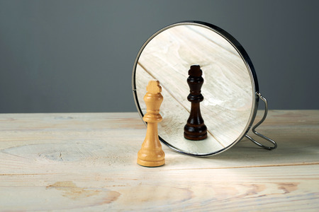 on mirrors: Black or white king chessmen in front of the mirror, concept about racism. Stock Photo