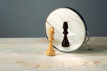 espejo: Piezas de ajedrez rey negro o blanco en frente del espejo, concepto sobre el racismo.