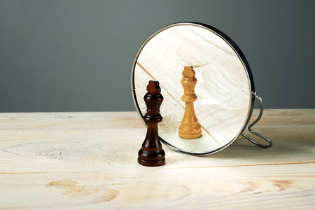 Black or white king chessmen in front of the mirror, concept about racism. Stock Photo