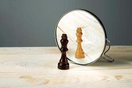 Zwarte of witte koning schaakstukken in de voorkant van de spiegel, concept over racisme. Stockfoto