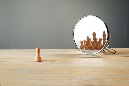 Usted no está solo. Piezas de ajedrez en frente del espejo