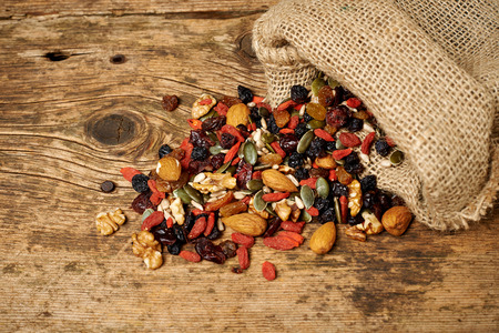 a seed: mix nuts seeds and dry fruits, on a wooden table Stock Photo
