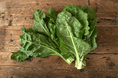 bunch of fresh spinach on a wooden table Stock Photo