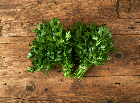 single object: bunches of fresh parsley on a wooden bench Stock Photo