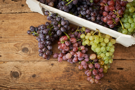 kitchen bench: bunch of fresh grapes on a wooden kitchen bench Stock Photo
