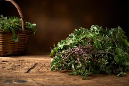 kitchen bench: fresh green leafy vegetable on a wooden kitchen bench.