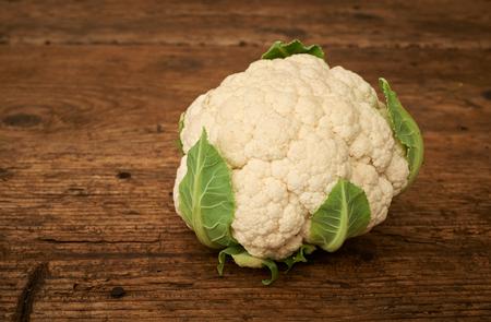 kitchen bench: Fresh raw cauliflower on a wooden kitchen bench. Stock Photo