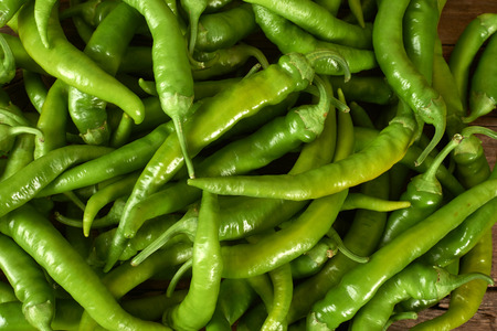 kitchen bench: many green peppers on a wooden kitchen bench. Stock Photo