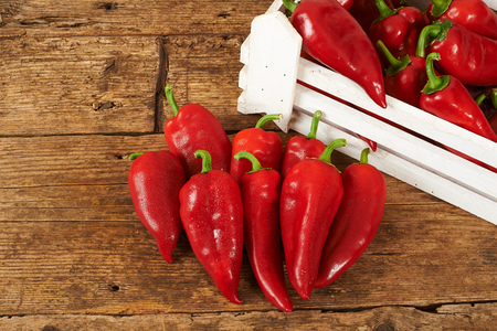 kitchen bench: many red peppers on a wooden kitchen bench. Stock Photo
