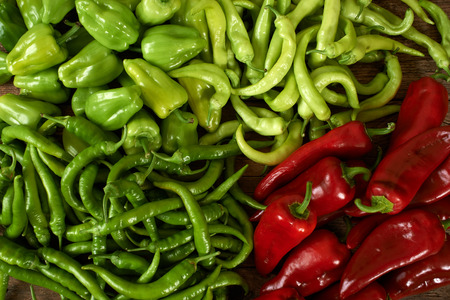 kitchen bench: many green and red peppers on a wooden kitchen bench. Stock Photo