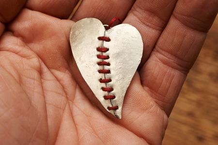 hilo rojo: coraz�n roto cosido con hilo rojo en una mano Foto de archivo