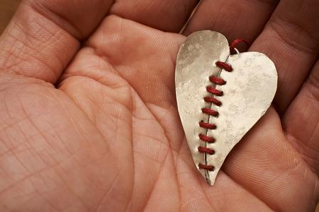 hilo rojo: corazón roto cosido con hilo rojo en una mano Foto de archivo