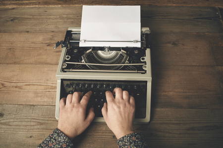 Woman is writing on an old typewriter. Imagens