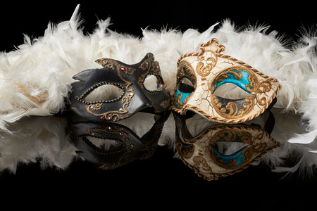 venetian carnival mask with white feathers on black background Imagens