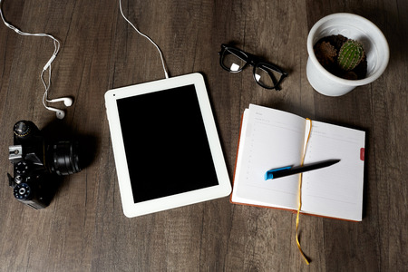 vintage camera, digital tablet with headphones, diary with a pen for notes, glasses and cactus lie on a brown wooden table, top view