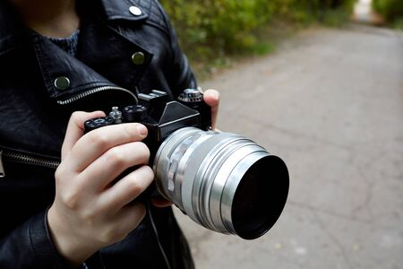 a woman in a leather jacket that holds a film retro camera in her hands, in the background a blurred asphalt alley and green trees
