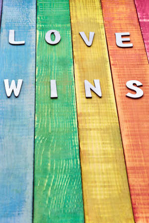 inscription love wins on wooden background in the color of lgbt community, there is free space for designer insert. suitable for articles about pride