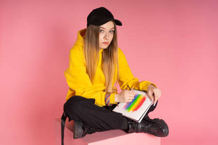 Inspired woman in yellow hoodie, black cap with pierced nose, painting a LGBTQ rainbow