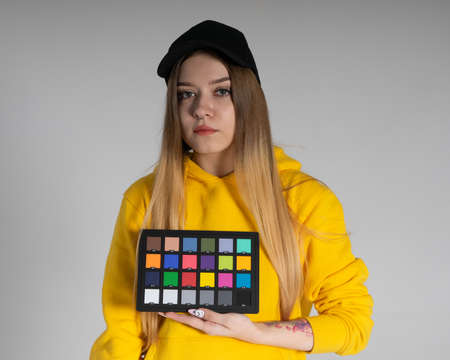 a girl in a yellow hoodie and a black cap is in the studio holding a color checker in her hands, the background behind her is gray