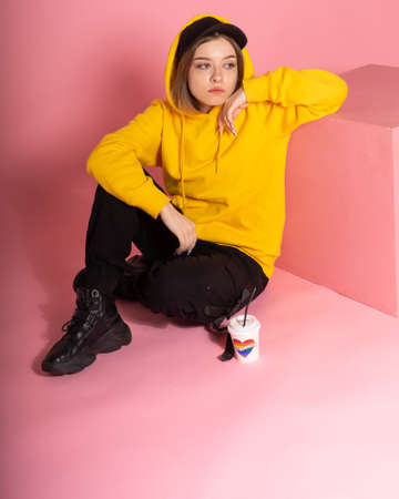 A sad young LGBT woman in a yellow hoodie and cap holds the visor, next to it there is a cup with a rainbow heart and the inscription love is love