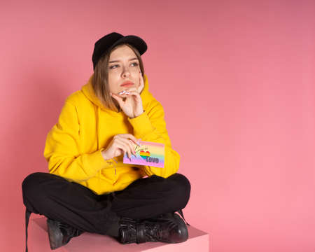 A pensive woman in a yellow hoodie and a black cap sits on a pink cube and holds a card with the words love is love, behind her is a rosy paper background