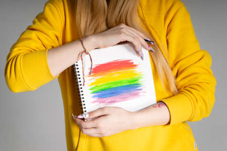 Woman holding a notepad with an LGBTQ rainbow in two hands