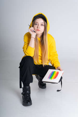 A pensive woman in a hoodie and a black cap holds a notebook with an LGBT rainbow painted on it. She sits on a white cyclorama in the studio