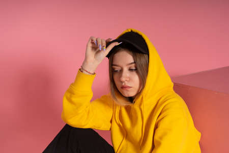 a girl in a black cap and yellow hoodie sits and misses, a pink background behind her