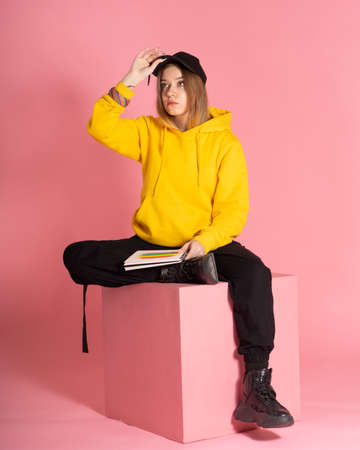 A pensive woman in a hoodie and a black cap holds a notebook with a drawn LGBTQ rainbow. She sits on a pink cube, behind her is the same background