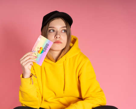 Sad woman wearing yellow hoodie jacket and ball cap holding a LGBTQ rainbow love card looking sad or melancholy on pink background.