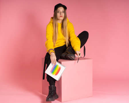A woman in a yellow hoodie, a black cap with a pierced nose, holds a notebook on which an LGBTQ rainbow is drawn