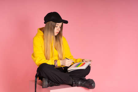 Woman in yellow hoodie, black cap with pierced nose, painting a LGBTQ rainbow
