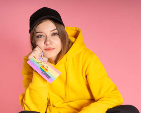 enamored woman in a yellow hoodie and a black cap holds a card with the words love is love, behind her is a rosy paper background Stock fotó