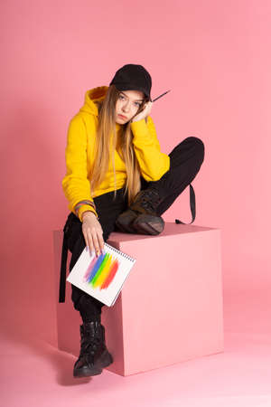 Sad woman in a yellow hoodie, a black cap with a pierced nose, holds a notebook on which an LGBTQ rainbow is drawn